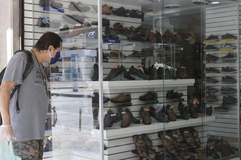 Homem olha vitrine de loja de calçados no Rio de Janeiro