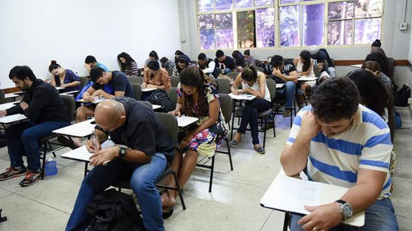 Jovens fazem prova em sala de aula