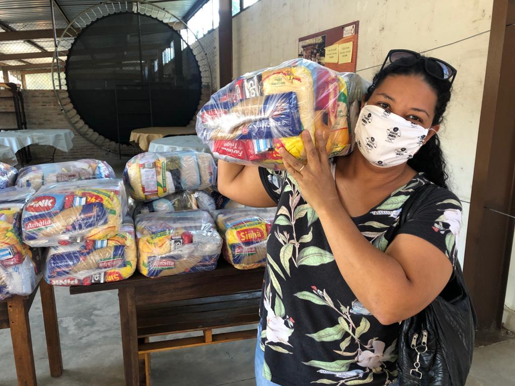 Mulher carrega uma cesta básica doada pelo Salão do Encontro de Betim (MG)