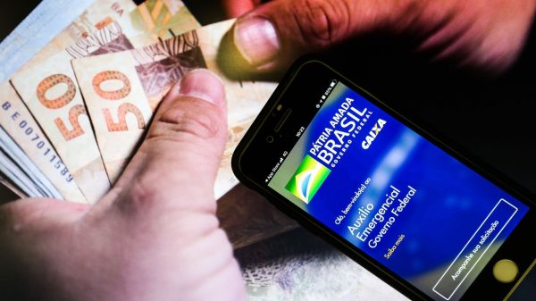 Dinheiro sendo contado, ao lado, um celular com o aplicativo Auxílio Emergencial do Governo Federal