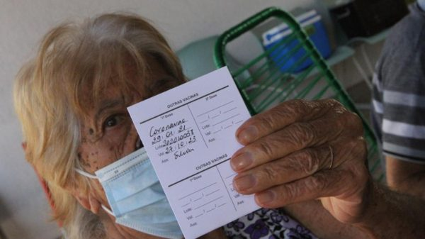 Mulher mostra cartão de vacinação contra a Covid-19 em Betim
