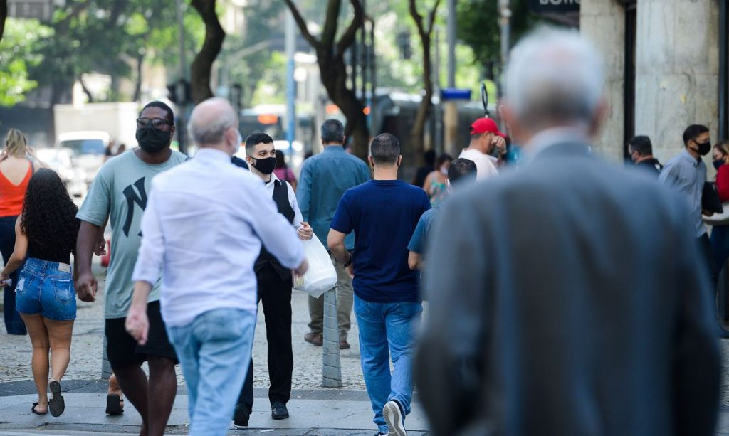 Pessoas com máscara caminham